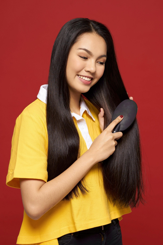 Hair care hacks: Asian woman brushing her long straight black hair