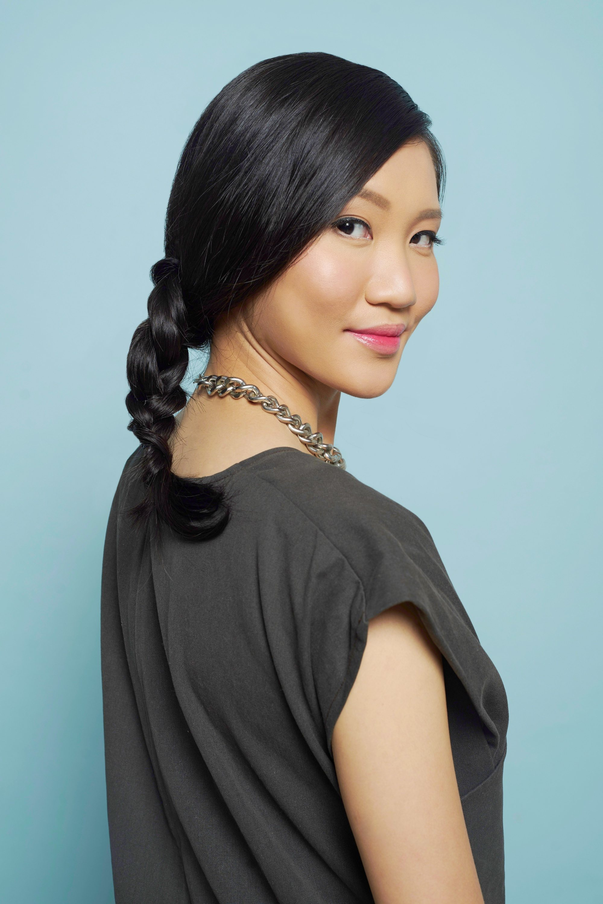 Hair care hacks: Asian woman with long black hair in a side braid wearing a dark gray top