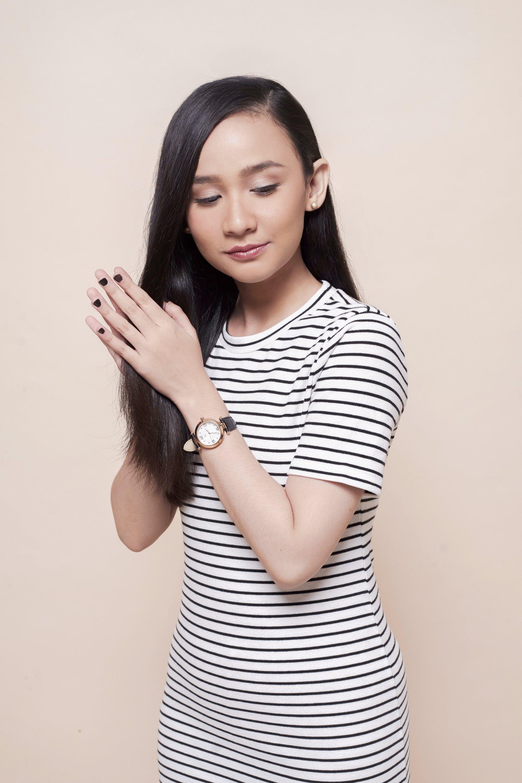Hair care hacks: Asian woman touching her long black hair wearing a striped dress