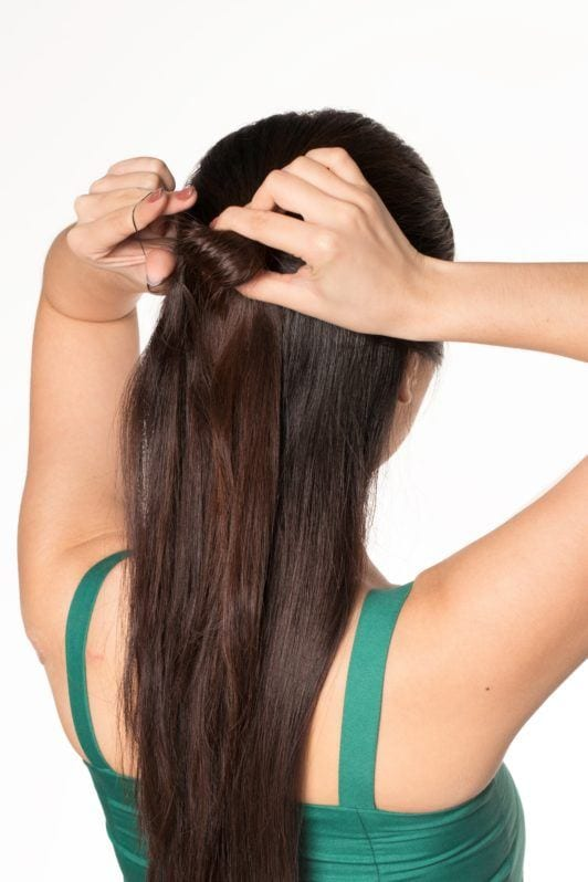 Half updo with bun: Back shot of an Asian woman with long dark hair tying her hair