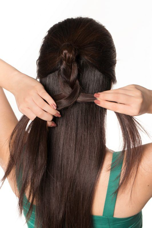 Half updo with bun: Back shot of an Asian woman styling her long dark hair