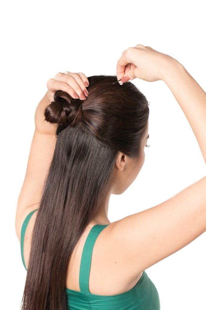 Half updo with bun: Back shot of an Asian woman with long dark hair pinning her half updo