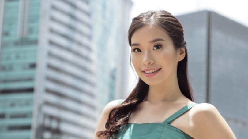 Closeup shot of an Asian woman with dark hair in half updo with bun wearing a green dress outdoors