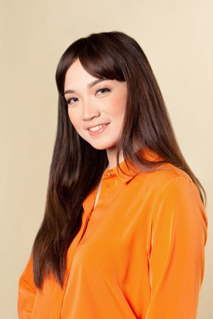 How to style blunt bangs for long hair: Asian woman with long dark hair with bangs wearing an orange blouse