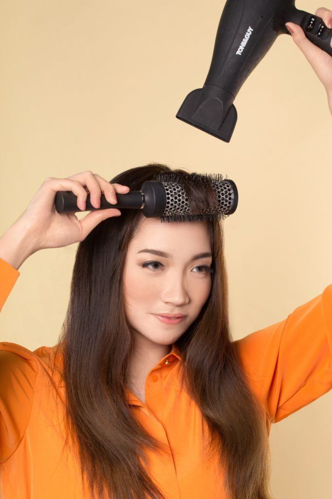How to style blunt bangs for long hair: Asian woman blow drying her long dark hair