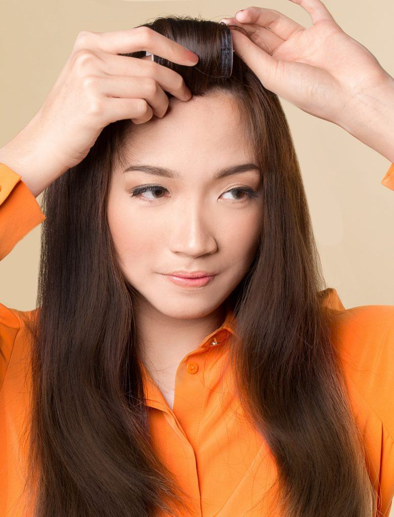 How to style blunt bangs: Asian woman with long dark hair wrapping her bangs around a velcro roller
