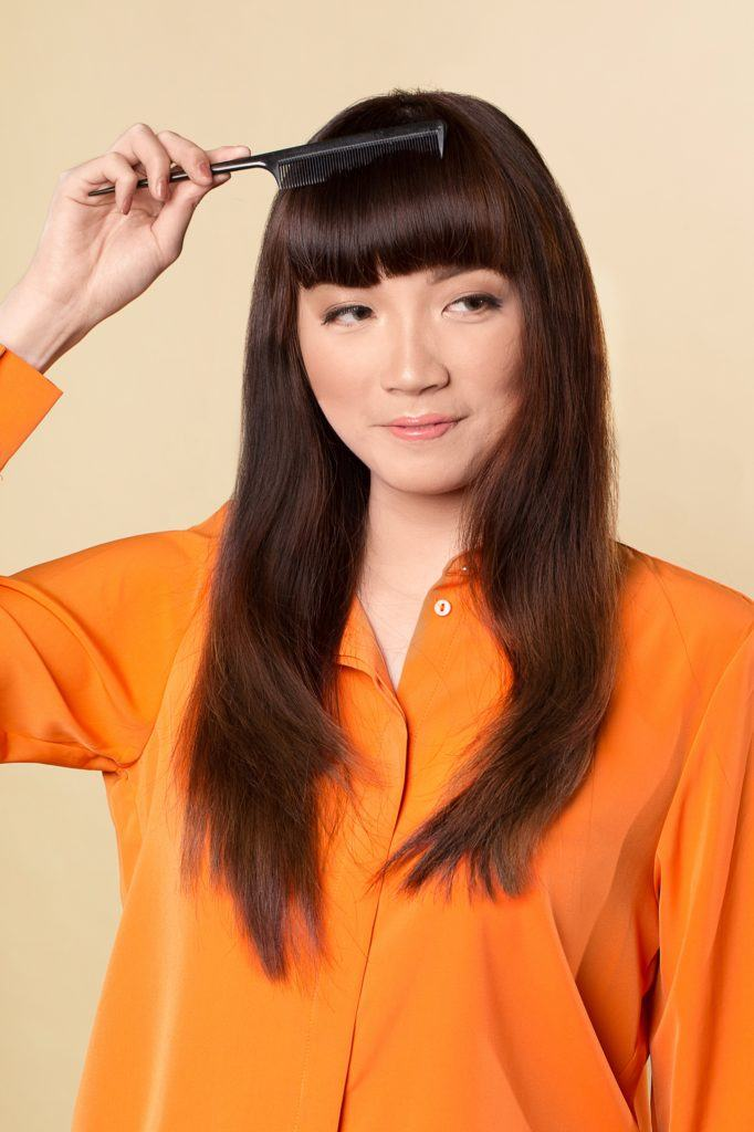 How to style blunt bangs for long hair: Asian woman with long dark hair combing her bangs