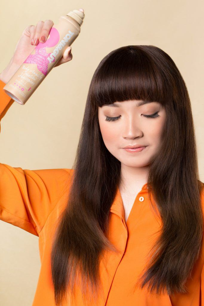 How to style blunt bangs for long hair: Asian woman spraying hairspray on her long dark hair with bangs