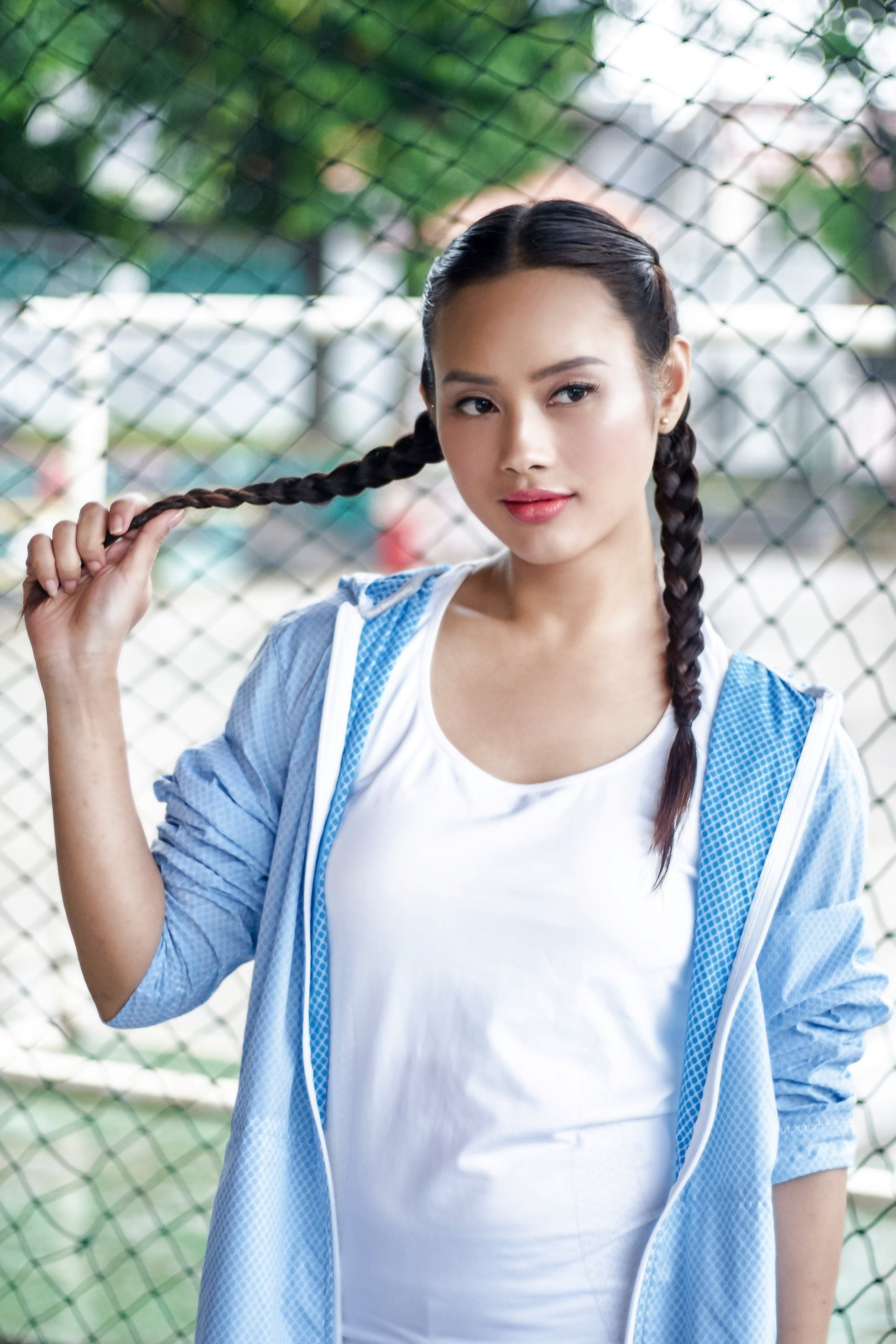 International Women's Day: Asian woman with long black hair in boxer braid wearing a sporty outfit outdoors