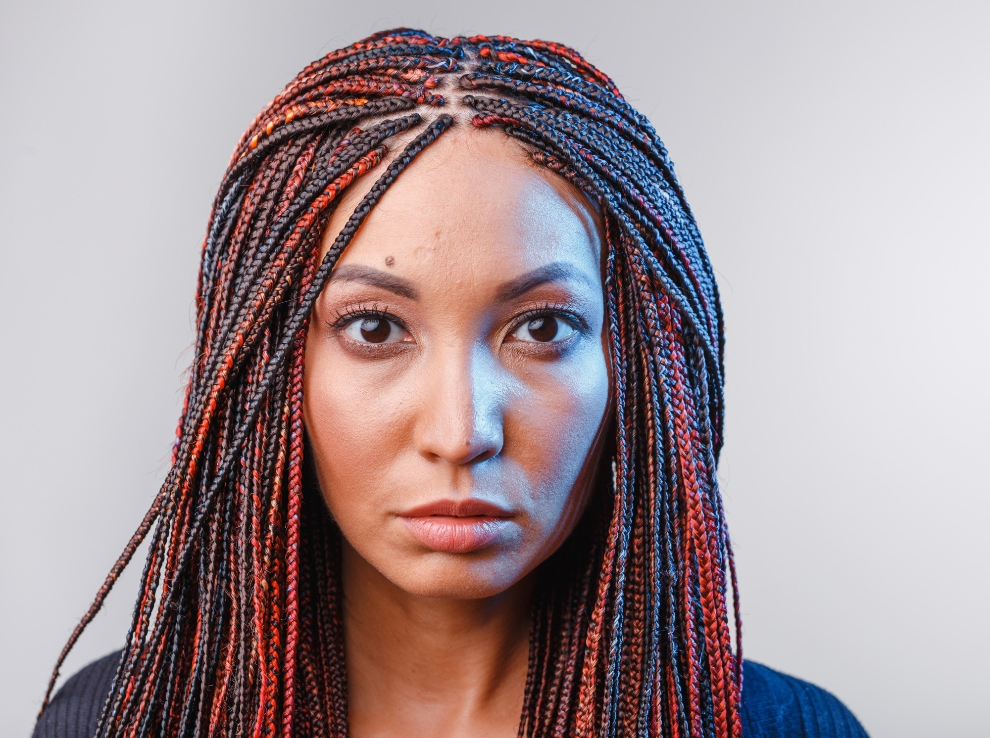 Micro braids: Closeup shot of a woman with long dyed hair in micro braids
