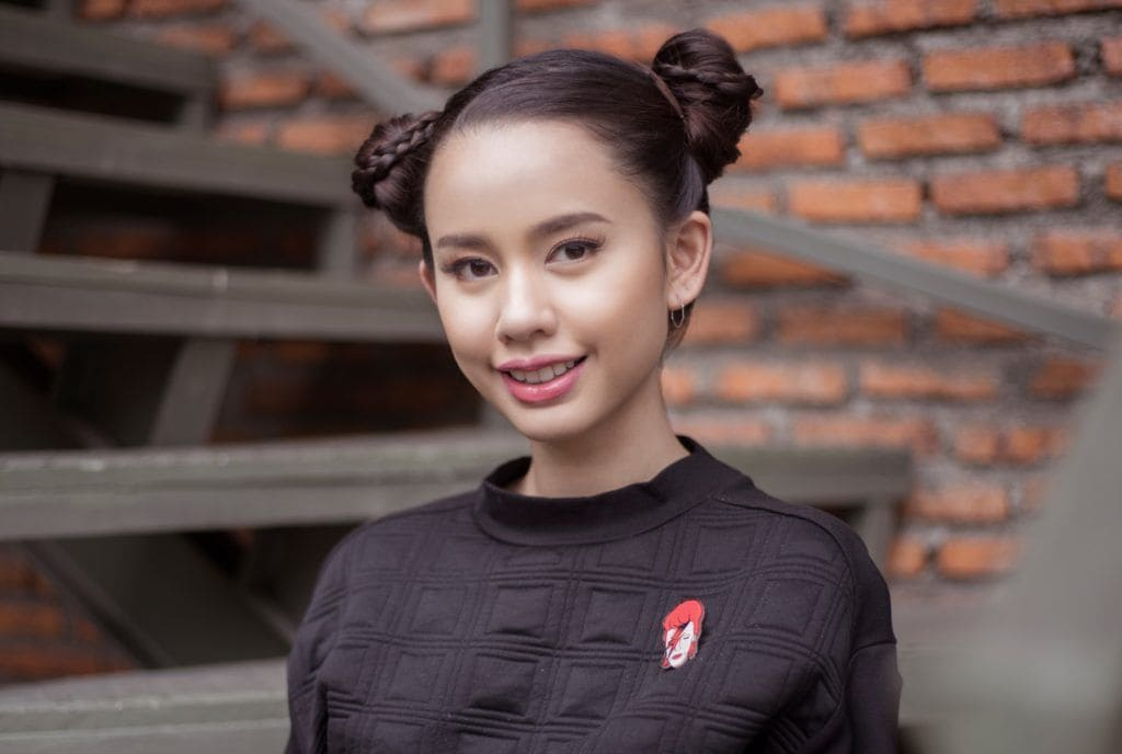 Micro braids: Closeup shot of an Asian woman with long dark hair in space bun wearing a black shirt outdoors