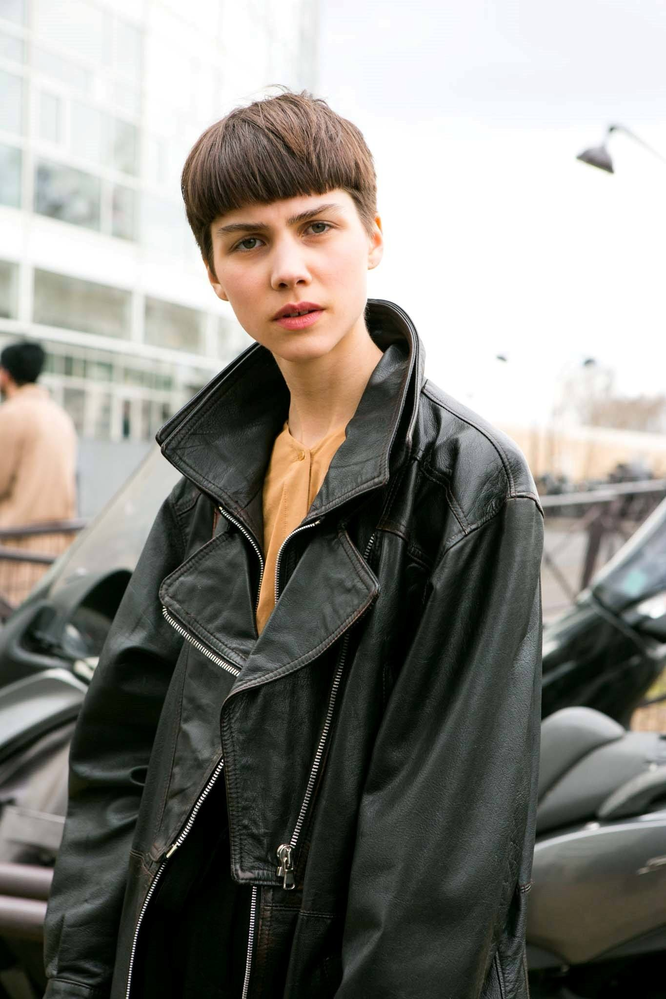 Caucasian woman with dark brown bowl cut hair wearing a black jacket outdoors
