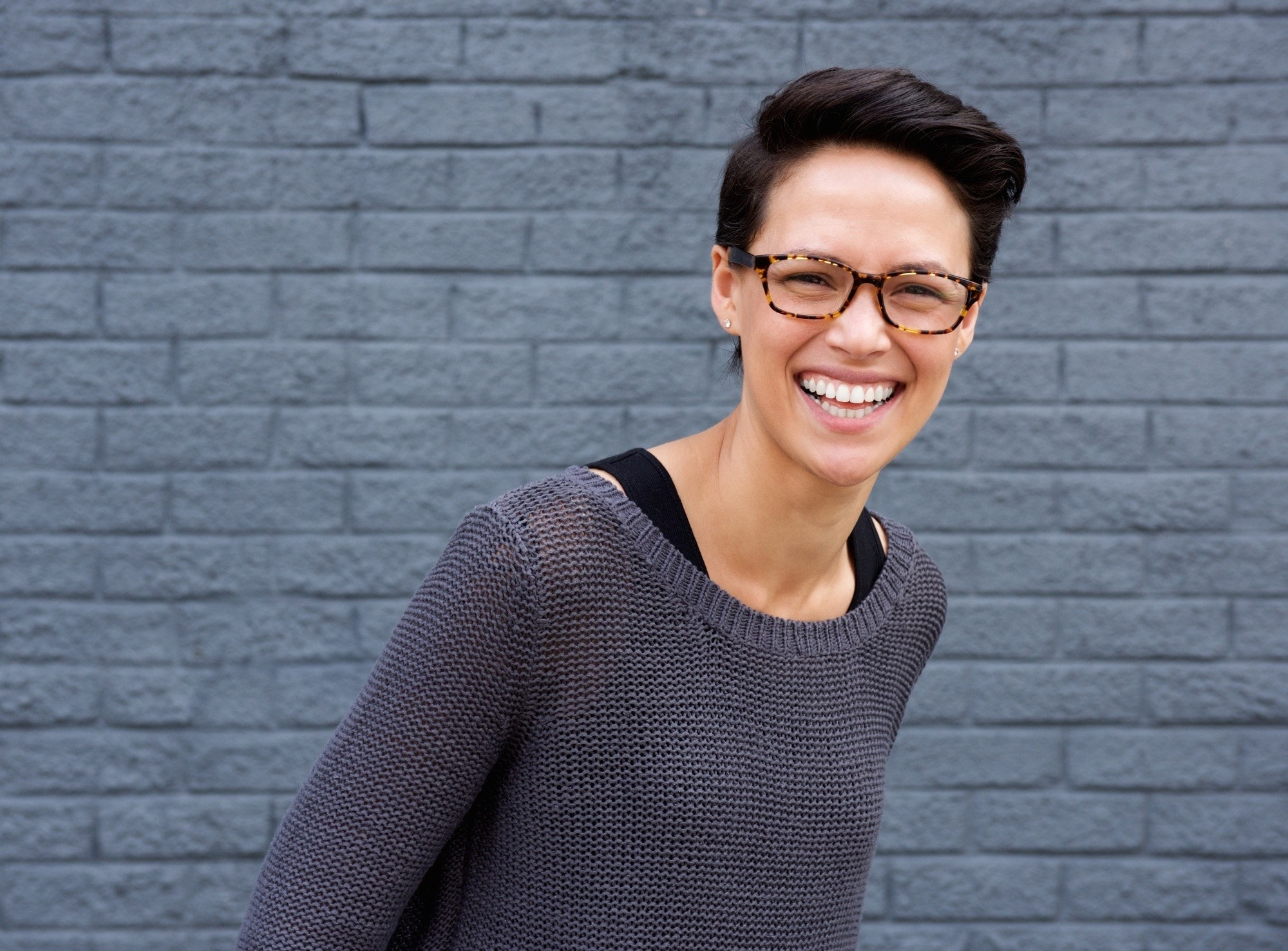 Short hairstyles for long faces: Woman with short dark hair wearing eyeglasses and gray sweater smiling