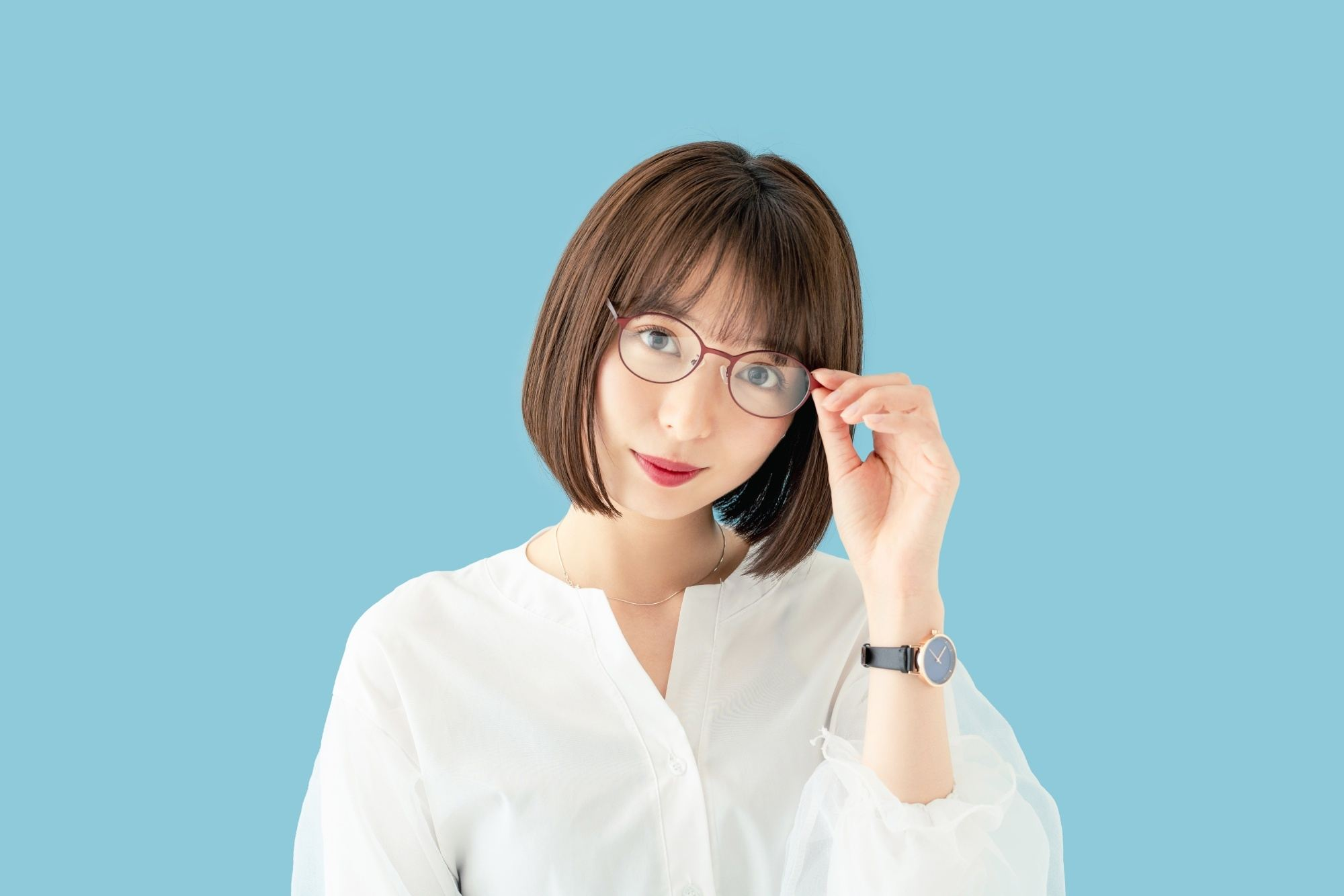 Asian woman with short dark hair with bangs wearing eyeglasses and a white blouse