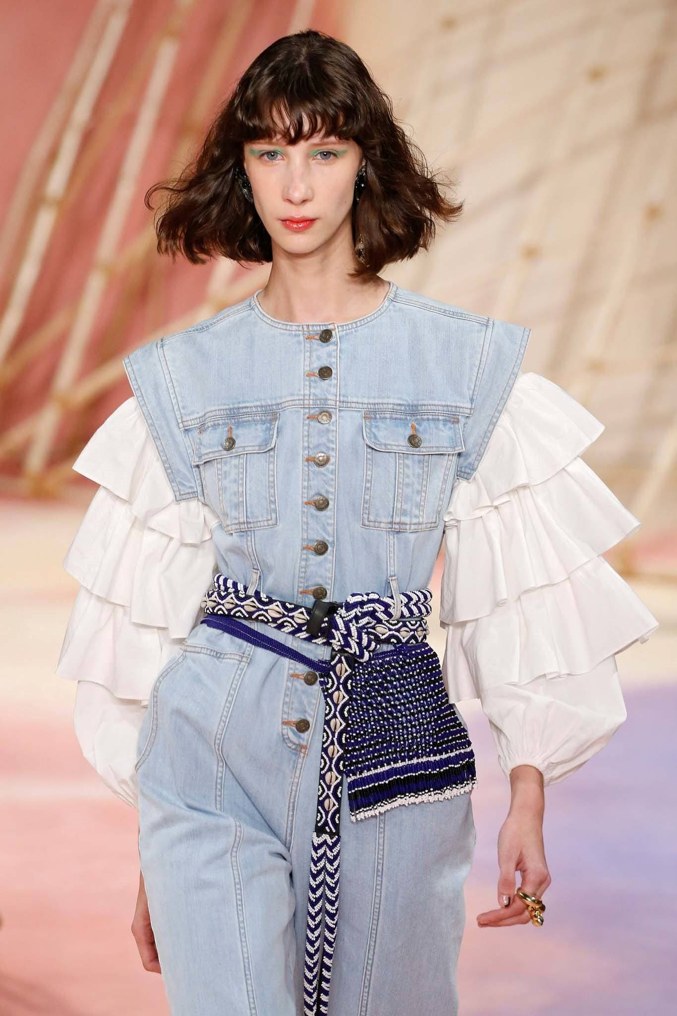 Woman with wavy bob with bangs wearing a light denim dress walking on the runway