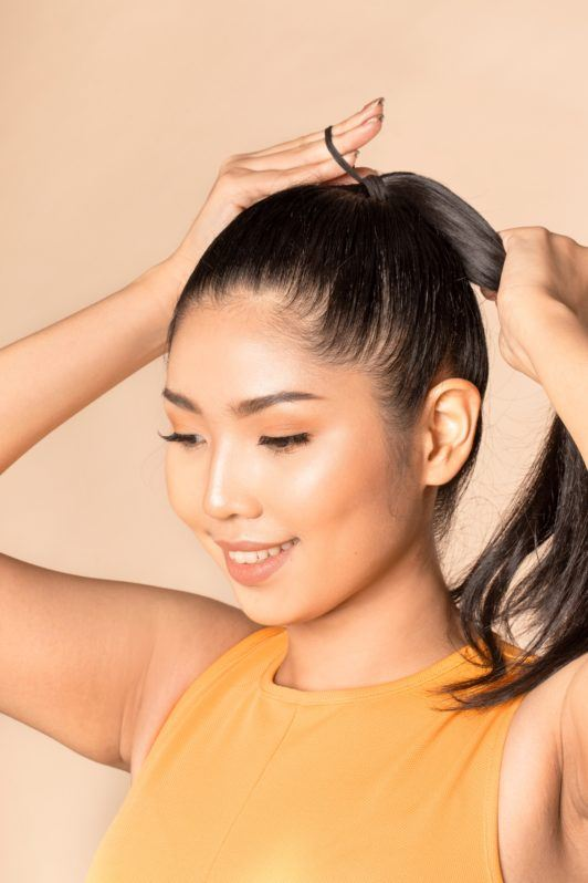 Sleek and fierce ponytail: Closeup shot of an Asian woman tying her long black hair in a ponytail