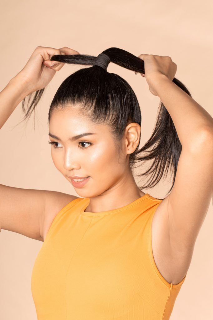 Sleek and fierce ponytail: Closeup shot of an Asian woman with long black hair styling her high ponytail