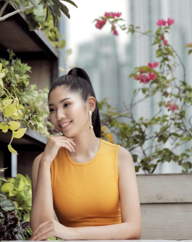 Sleek and fierce ponytail: Closeup shot of an Asian woman with long black hair in high ponytail wearing a mustard dress on a rooftop lounge