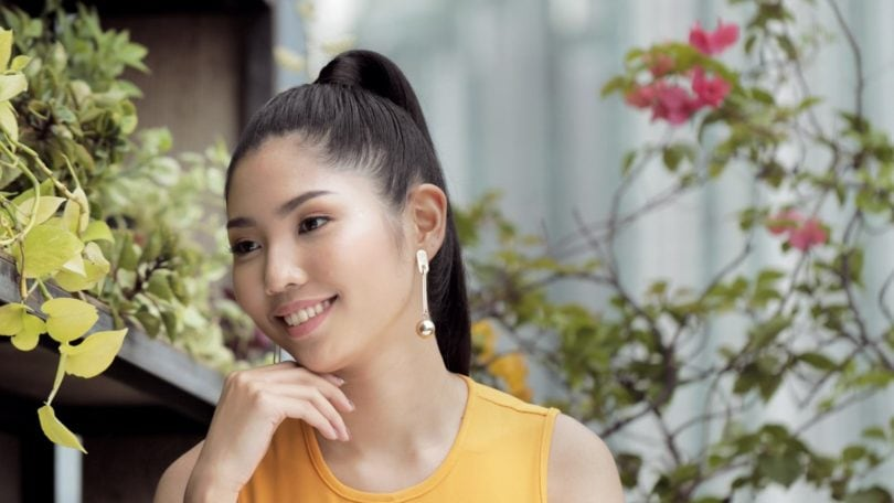 Sleek and fierce ponytail: Closeup shot of an Asian woman with long black hair in high ponytail wearing a mustard dress at a rooftop lounge