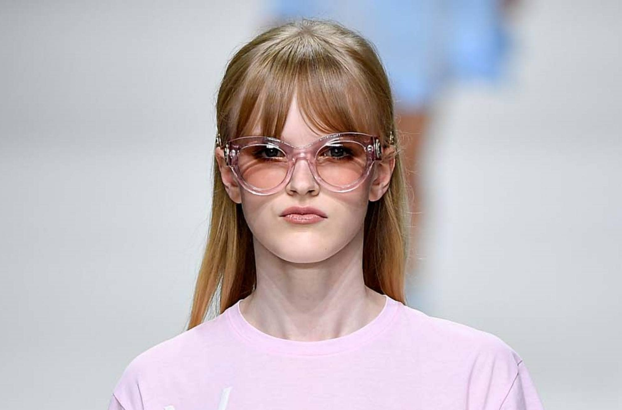 Sleek tied hair: Closeup shot of a Caucasian woman with long brown hair with bangs wearing shades and pink shirt