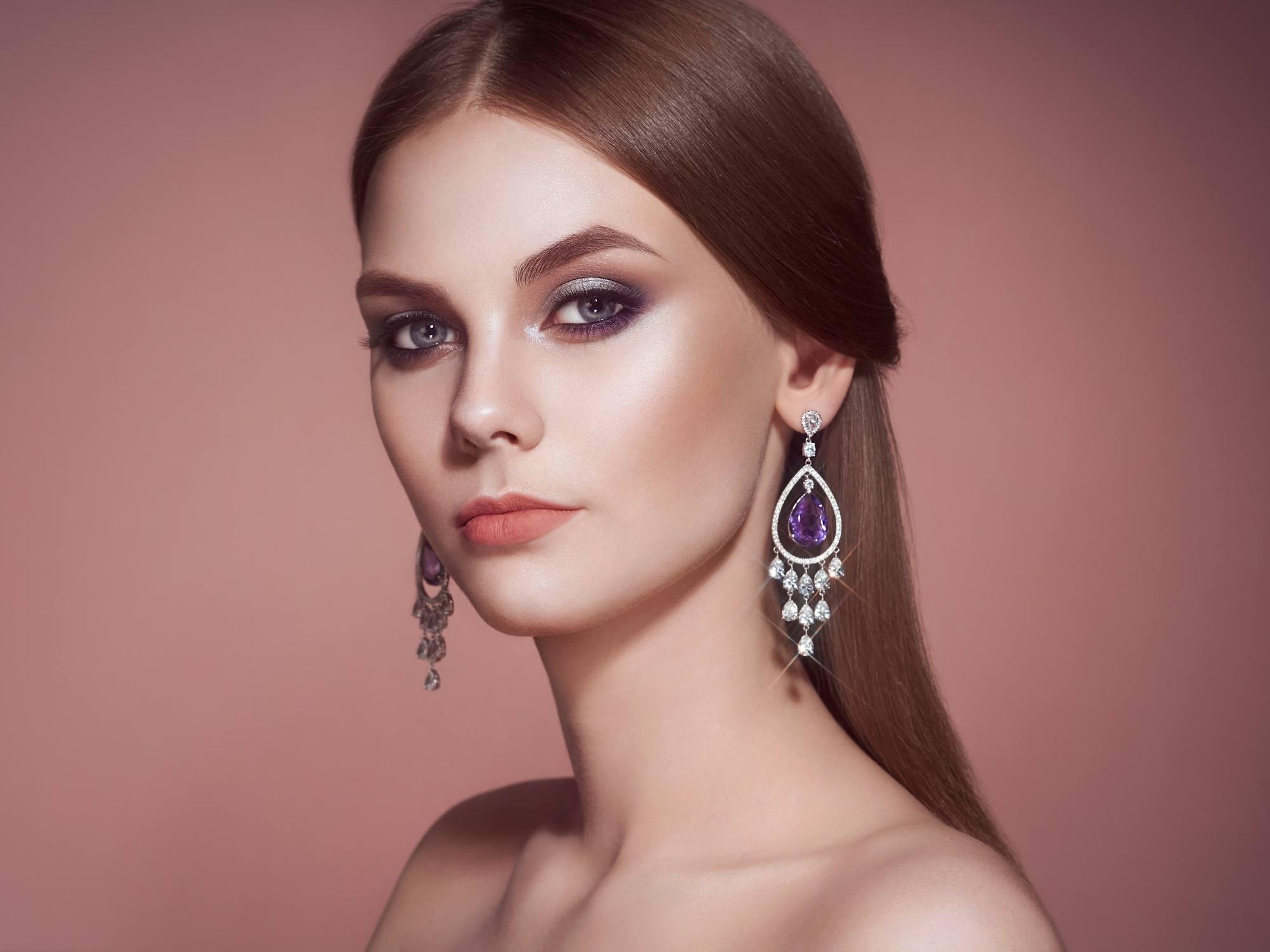 Sleek tied hair: Closeup shot of a Caucasian woman with long brown hair in half ponytail wearing long earrings