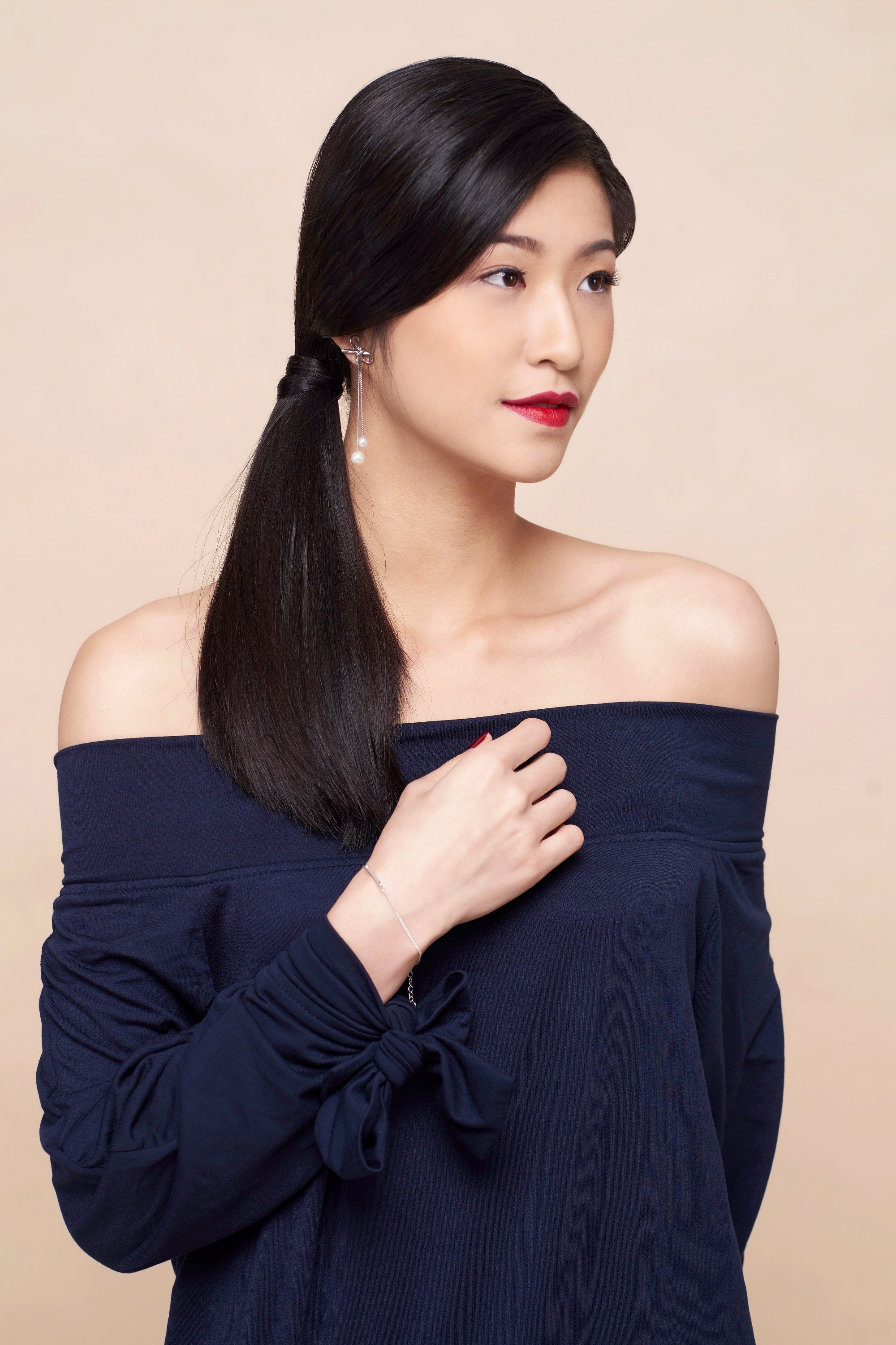 Sleek tied hair: Asian woman with long black hair in a side ponytail wearing a dark blue off-shoulder blouse
