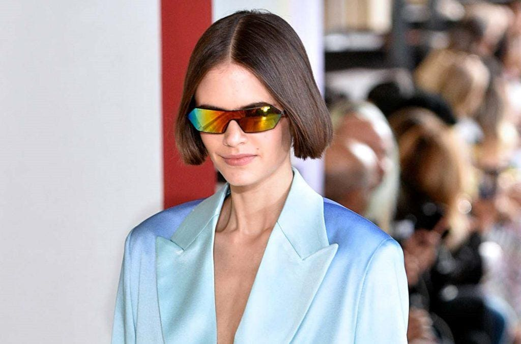 Straight bob: Closeup shot of a woman with short straight dark hair wearing sunglasses and blue suit