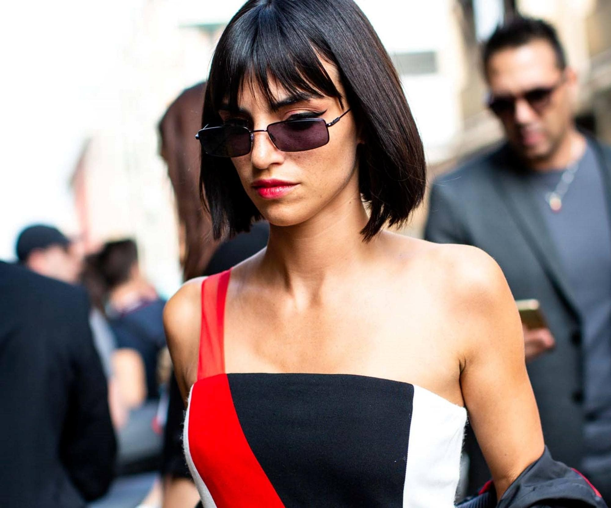Straight bob: Closeup shot of a woman with short straight black hair with bangs wearing a tube top outdoors
