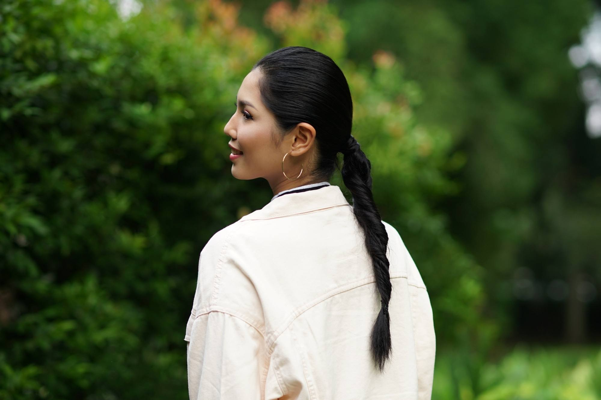 Hair types: Back shot of an Asian woman with long black hair in a double rope braid ponytail wearing a white jacket outdoors
