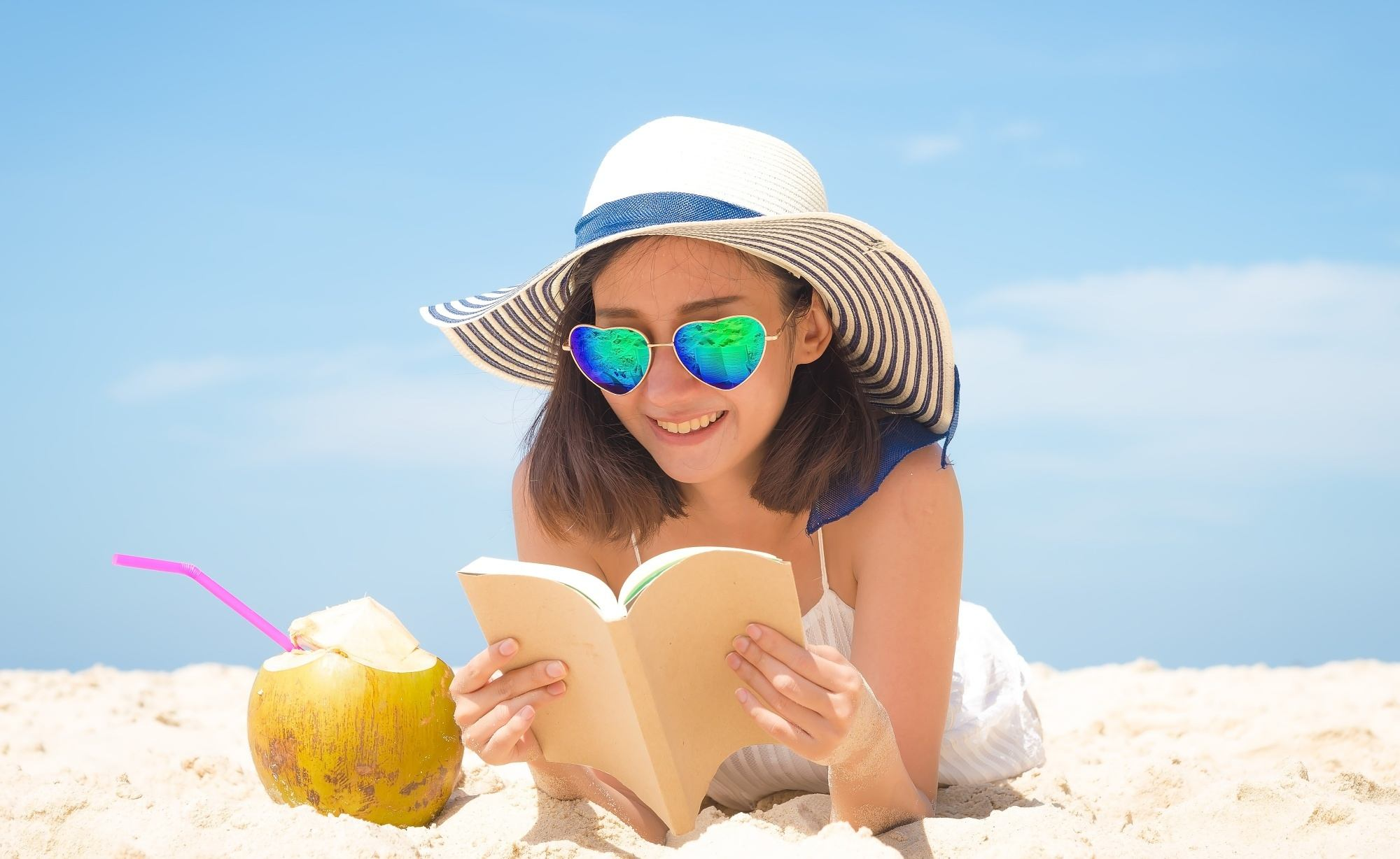 Great summer hair: Woman wearing a hat and sunglasses reading a book on the beach