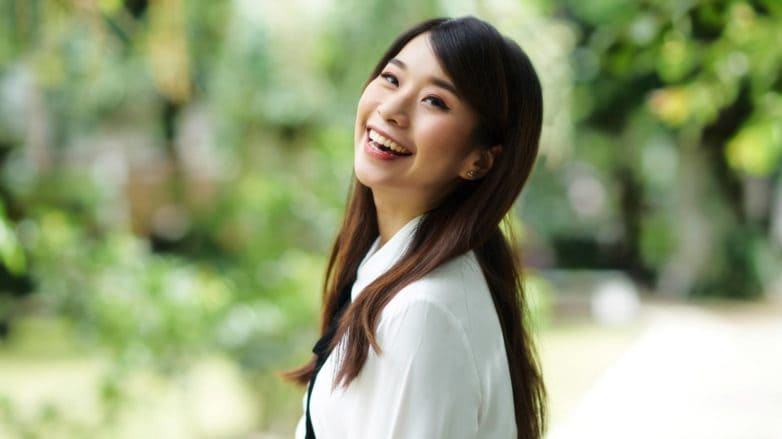 Summer-ready hair: Asian girl with long dark hair smiling outdoors