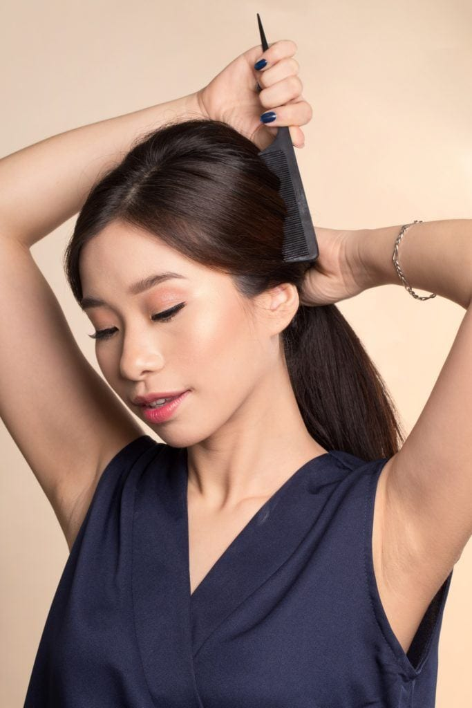 Vintage ponytail: Asian woman combing her long black hair to put into a ponytail