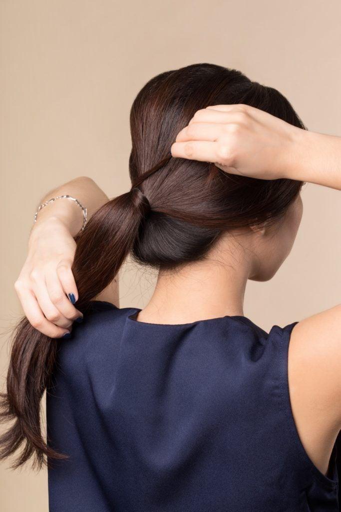 Vintage PonytaiL: Back shot of an Asian woman putting her long dark hair in a sleek ponytail