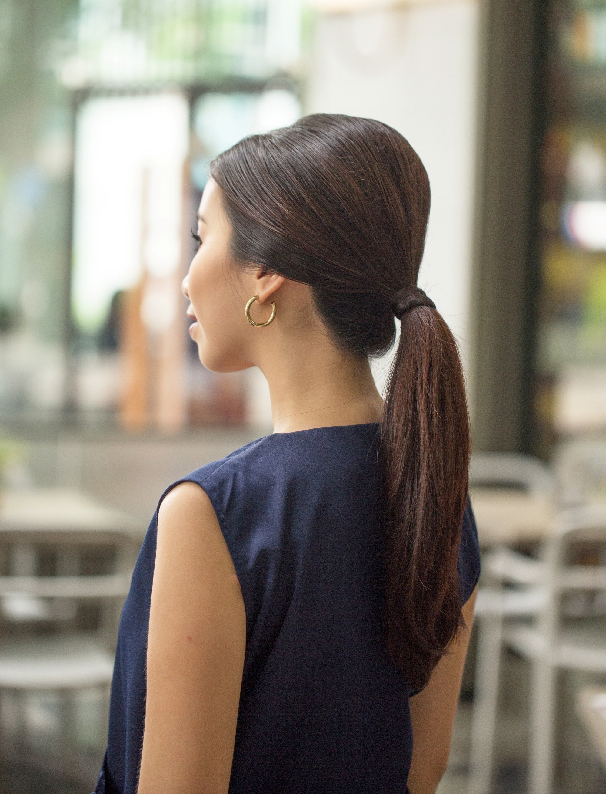Vintage ponytail: Side view shot of an Asian woman with long dark hair in a vintage ponytail standing in an outdoor restaurand