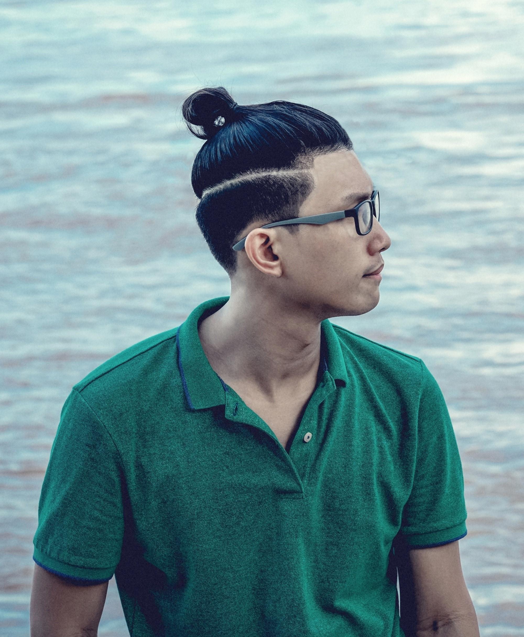 Asian man bun: Asian man with black hair in a half up bun wearing a green shirt by the sea