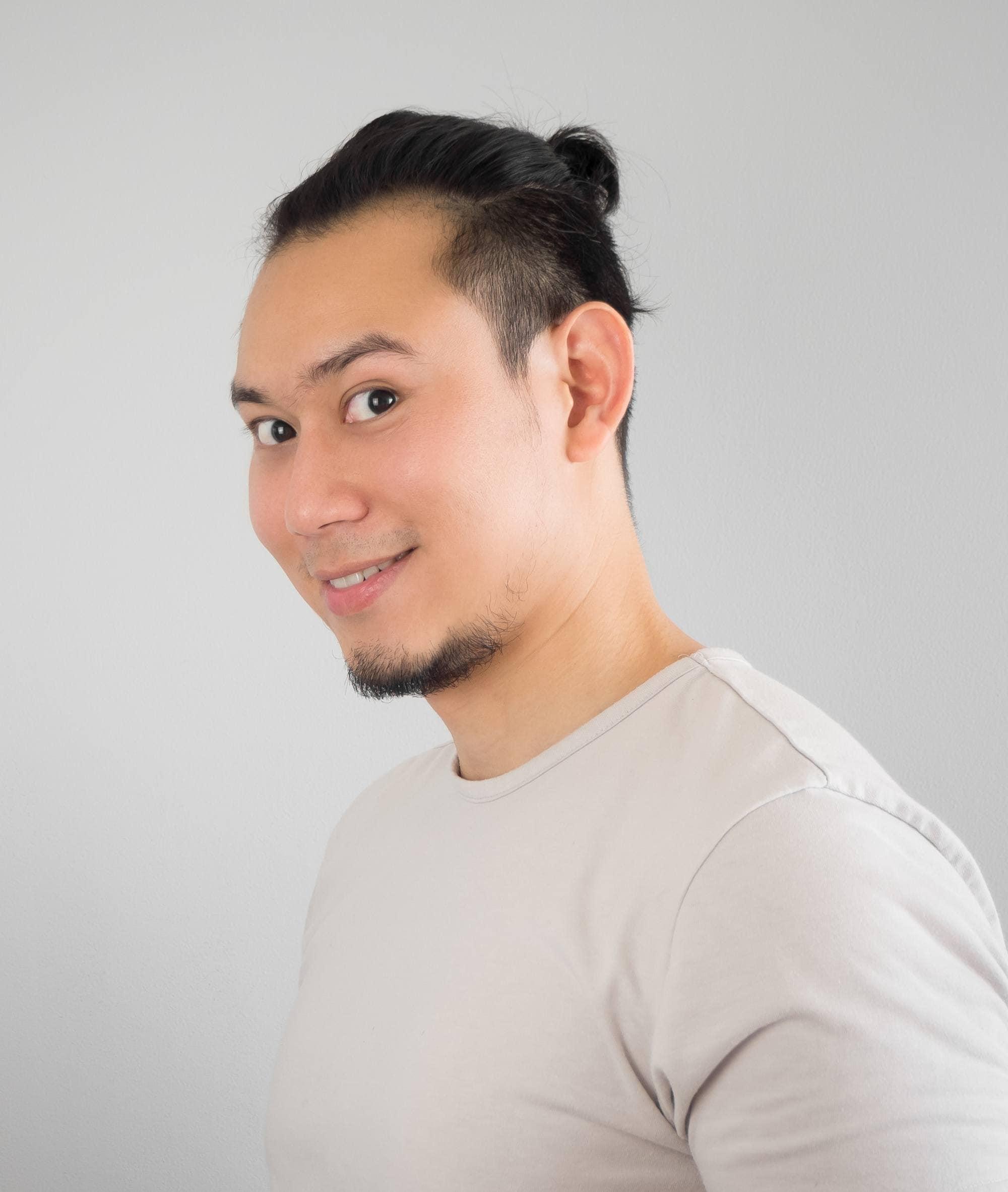 Asian man bun: Asian man smiling with black hair in a mini bun wearing a gray shirt