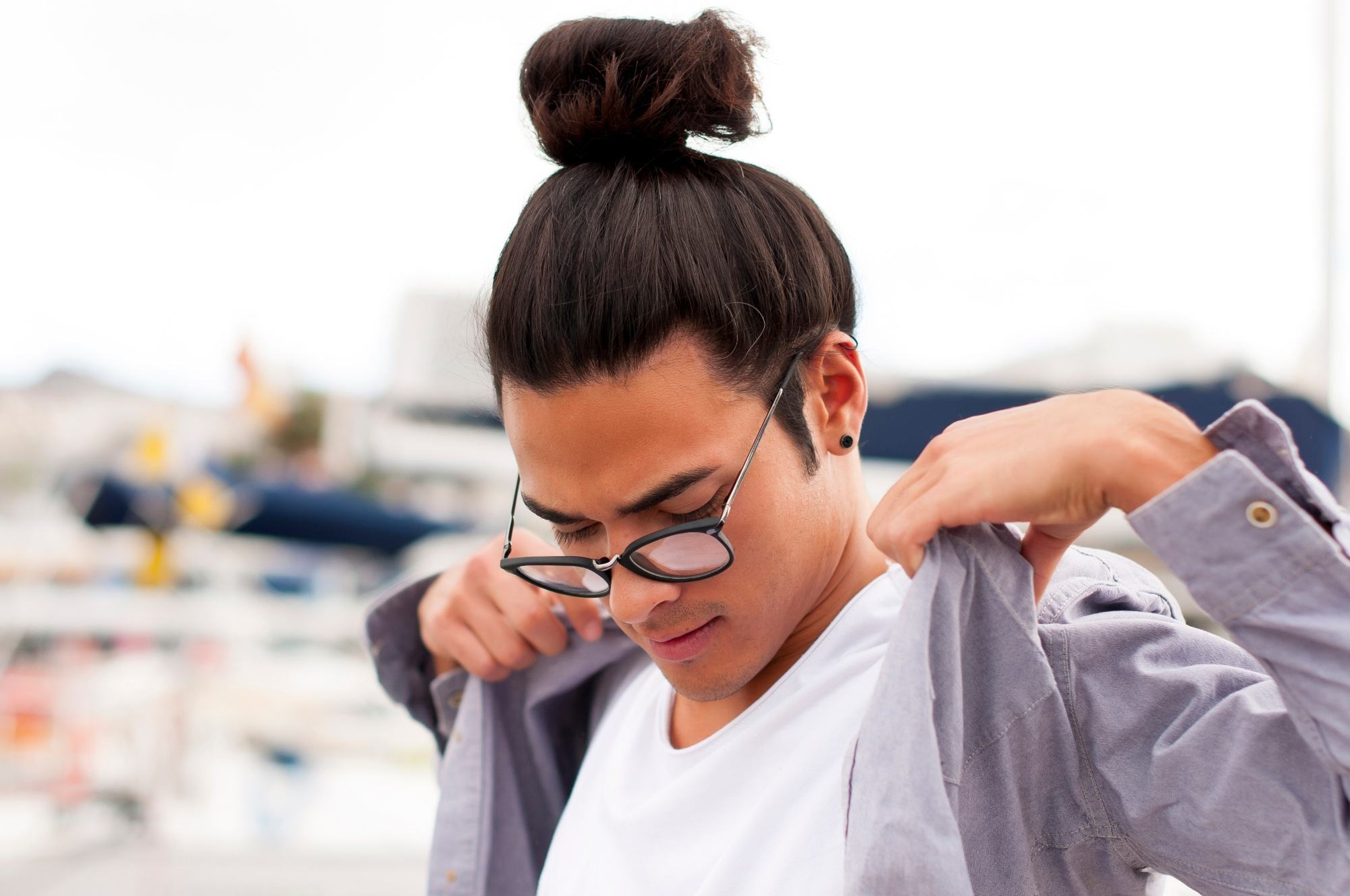 Asian man bun: Man with brown skin with long dark hair in a top knot