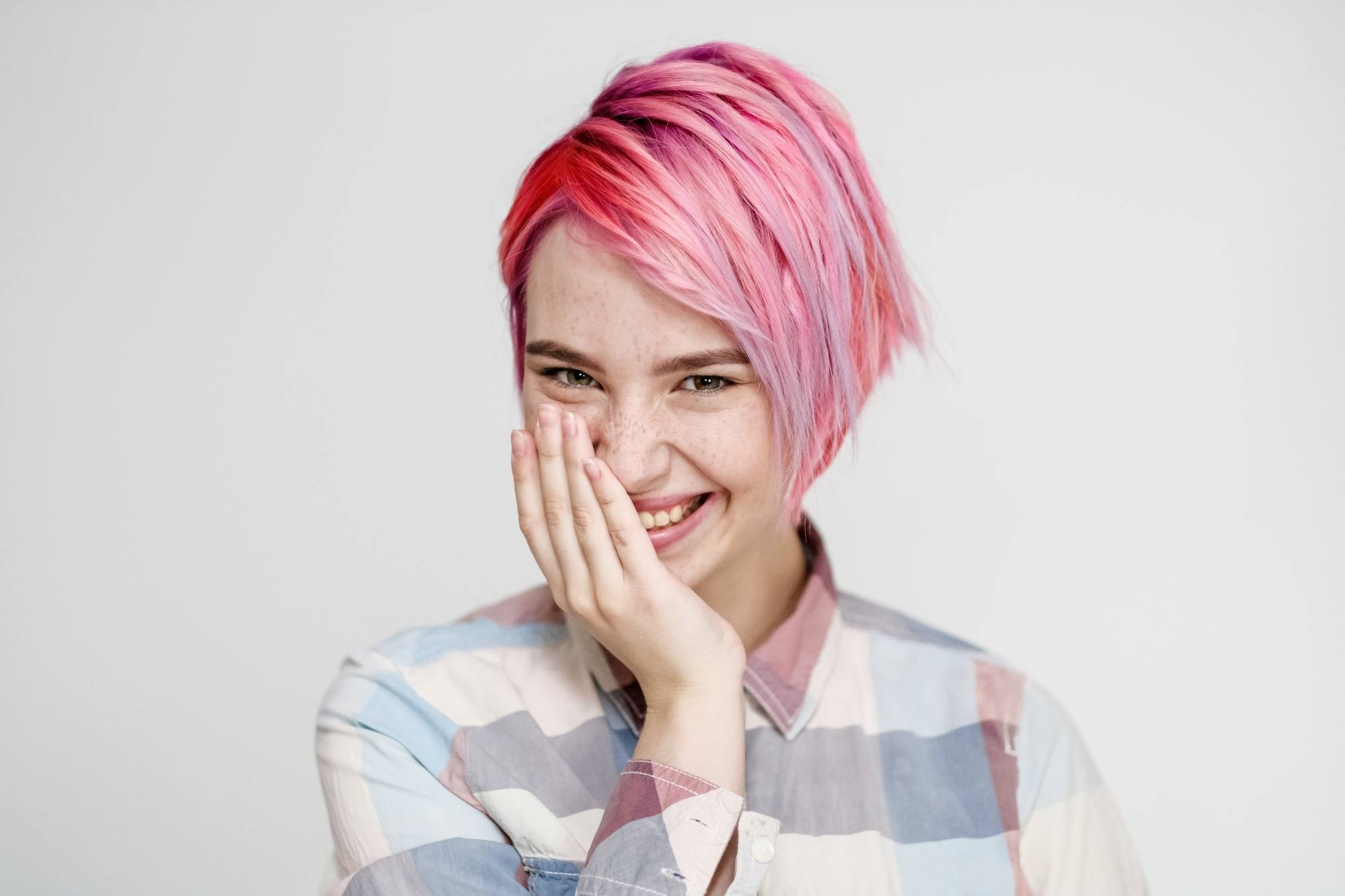 Bob haircuts for fine hair: Woman with short pink hair touching her face laughing