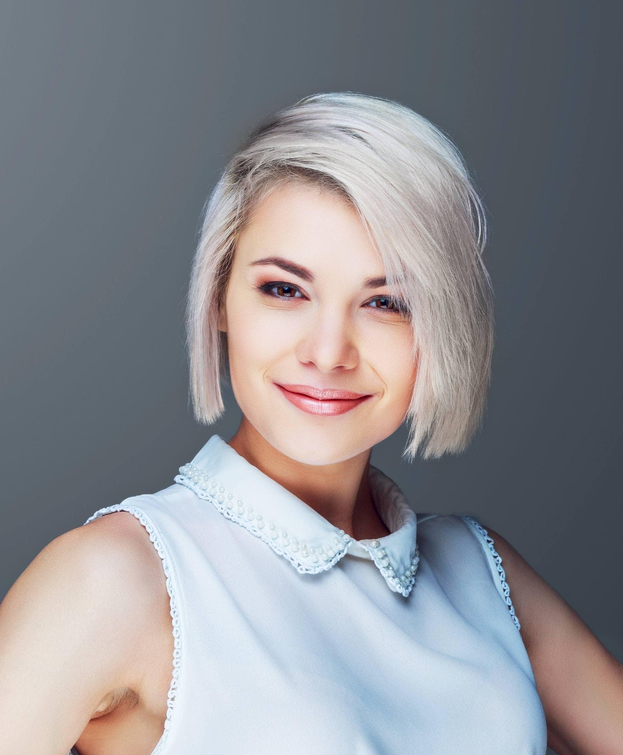 Bob haircuts for fine hair: Closeup shot of a Caucasian woman with short blonde hair smiling