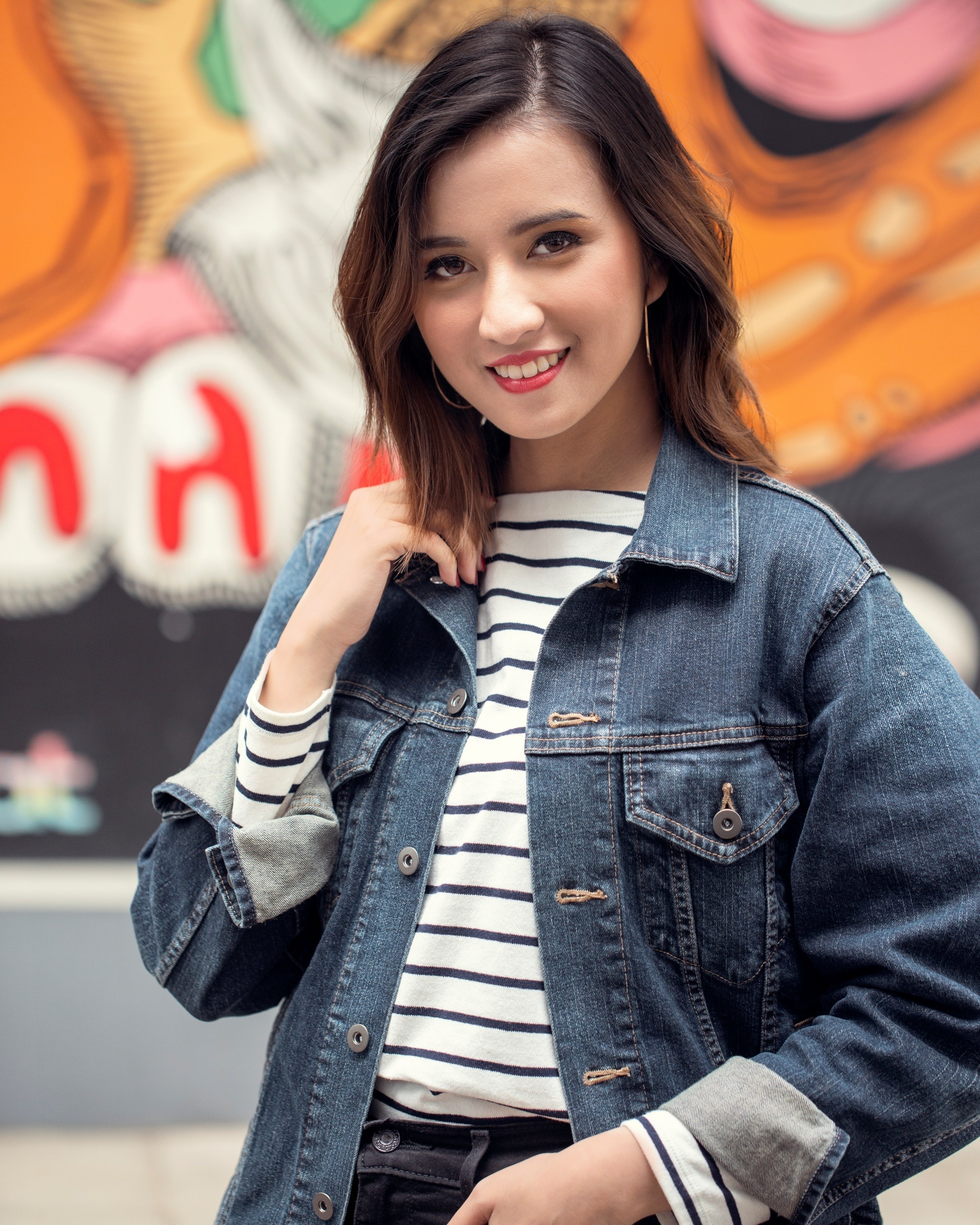 Bob haircuts for fine hair: Asian woman with dark brown messy layered bob wearing a denim jacket in front of a street mural