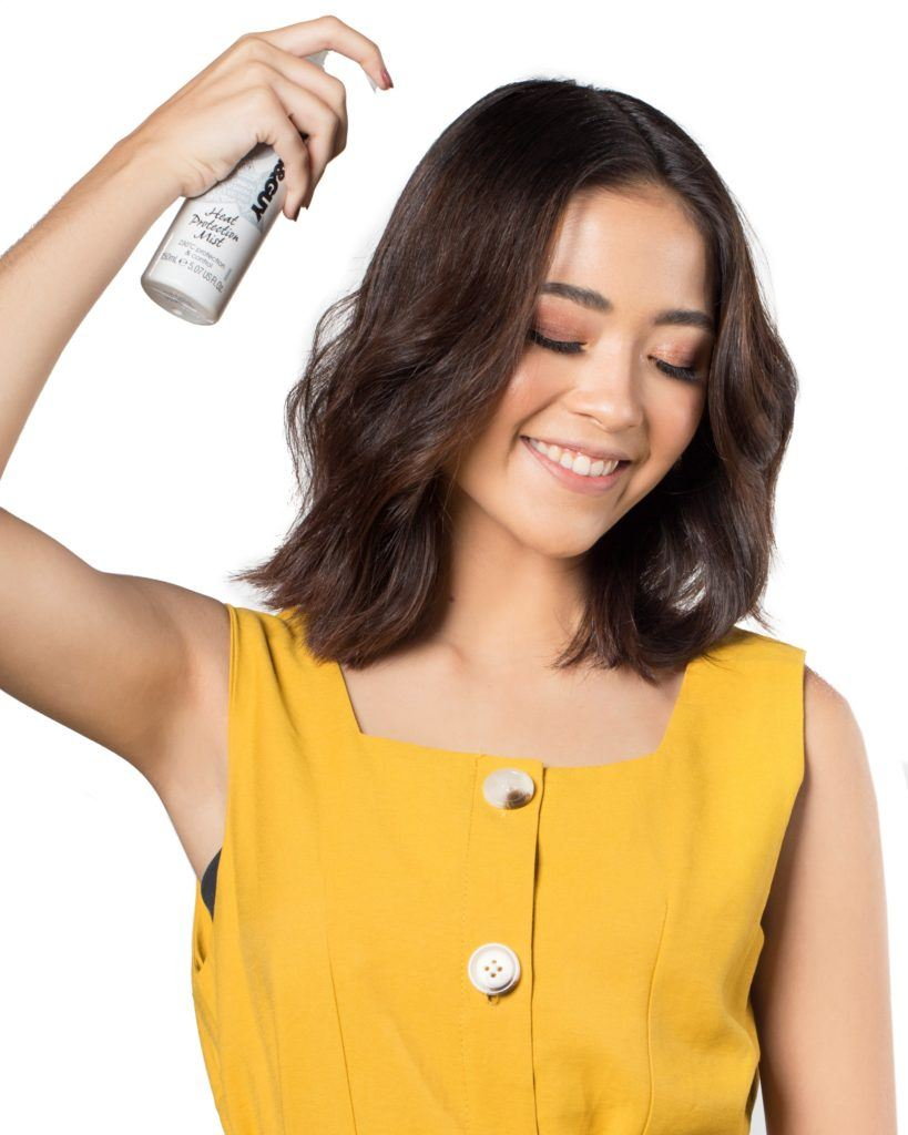 Bobby pin hair crown: Asian woman spraying heat protectant on her shoulder-length dark hair and smiling