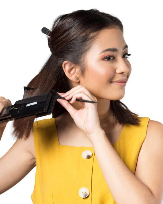 Bobby pin hair crown: Asian woman ironing her dark shoulder-length hair wearing a mustard-colored top
