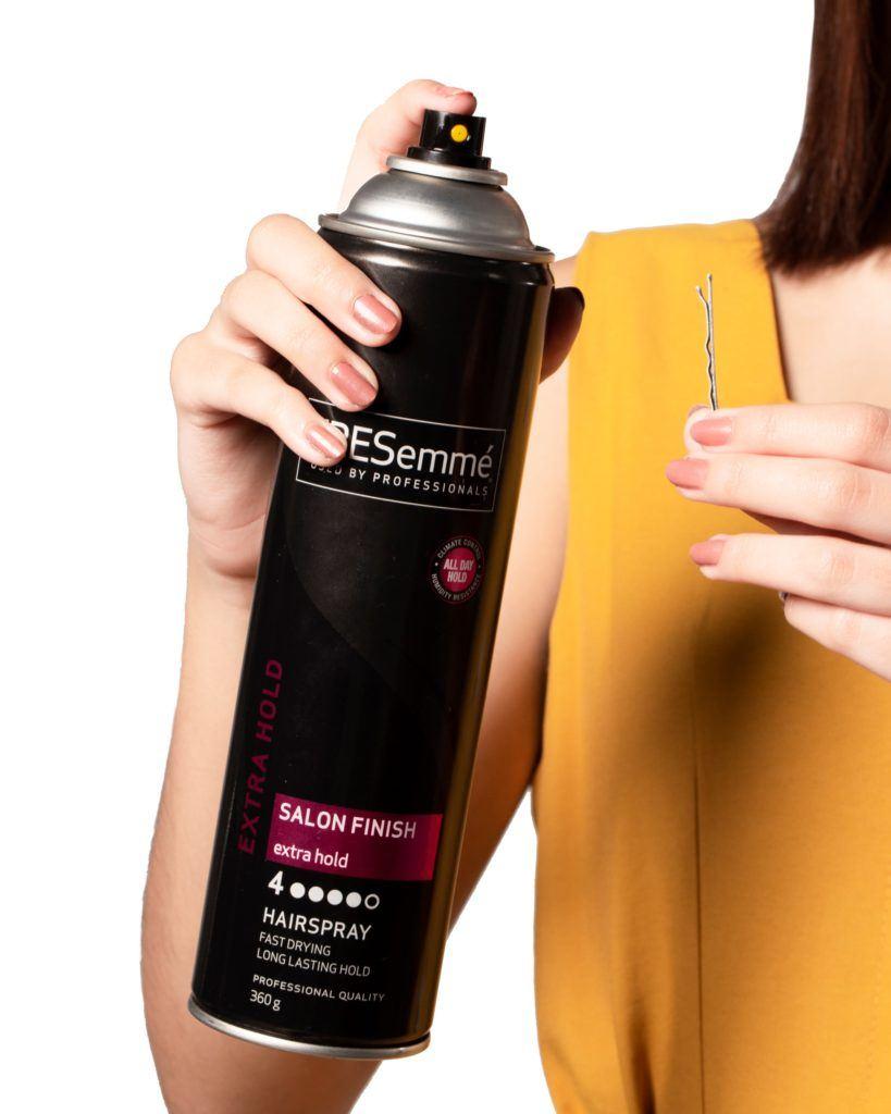 Bobby pin hair crown: Closeup shot of hands of an Asian woman spraying hairspray on a bobby pin
