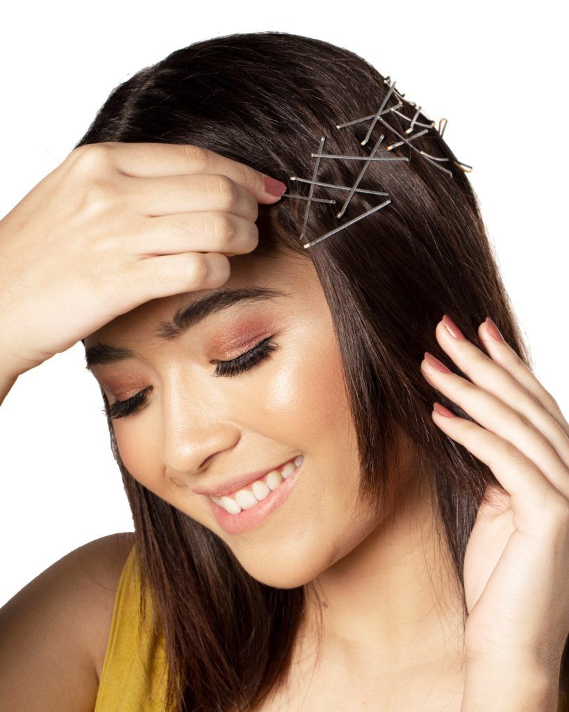 Bobby pin hair crown: Closeup shot of an Asian woman putting pins on her dark hair and smiling