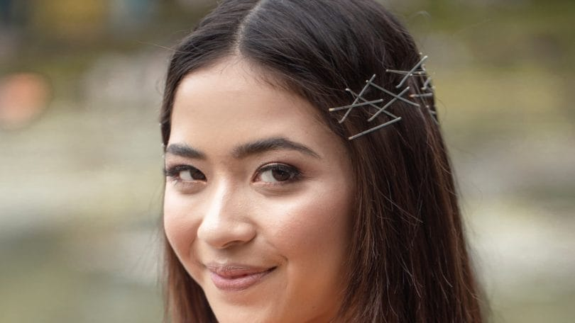 Bobby pin hair crown: Closeup shot of an Asian woman with bobby pins on her dark shoulder-length hair smiling outdoors