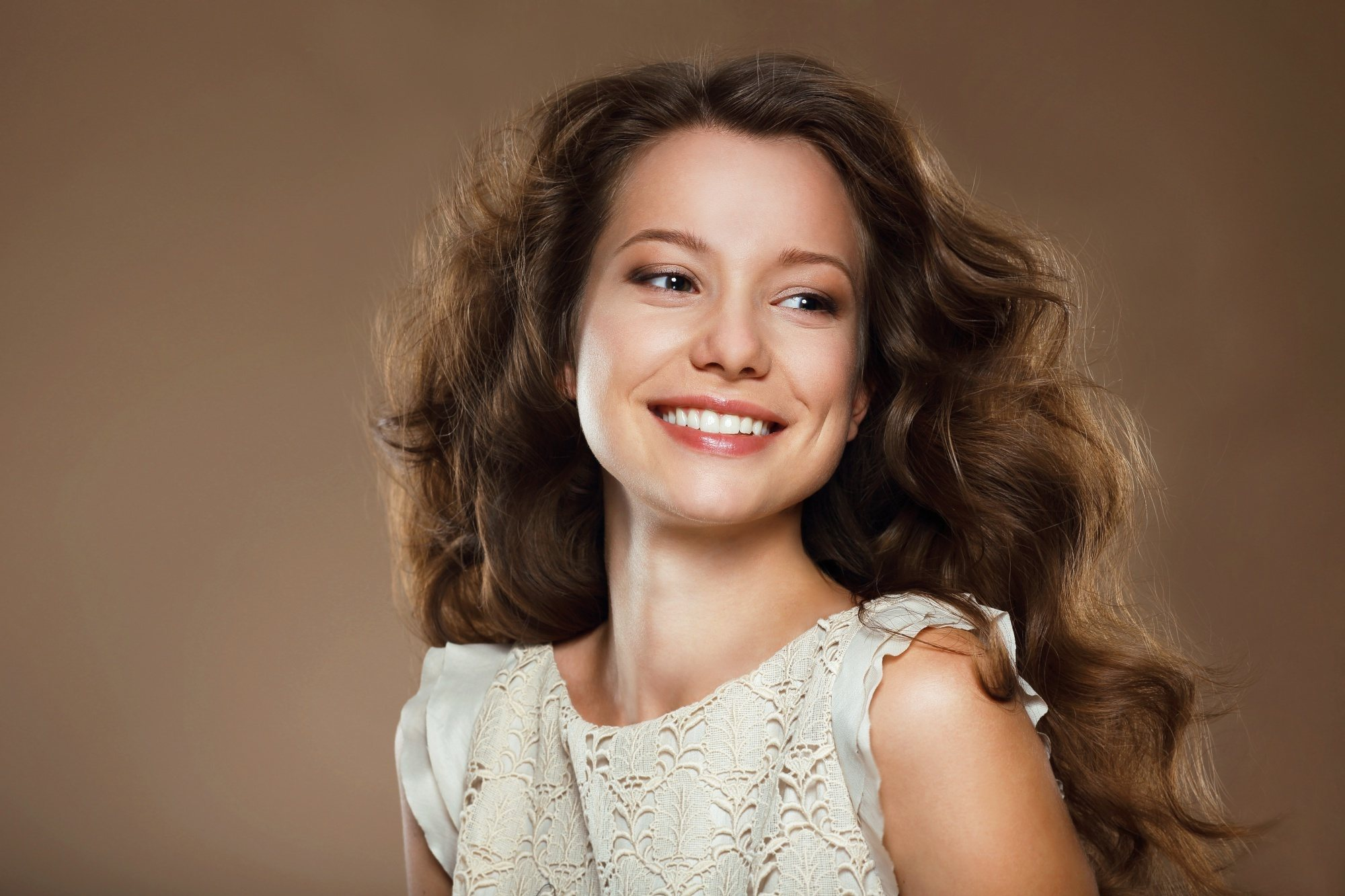 Caramel hair color: Woman with long brown curly hair smiling
