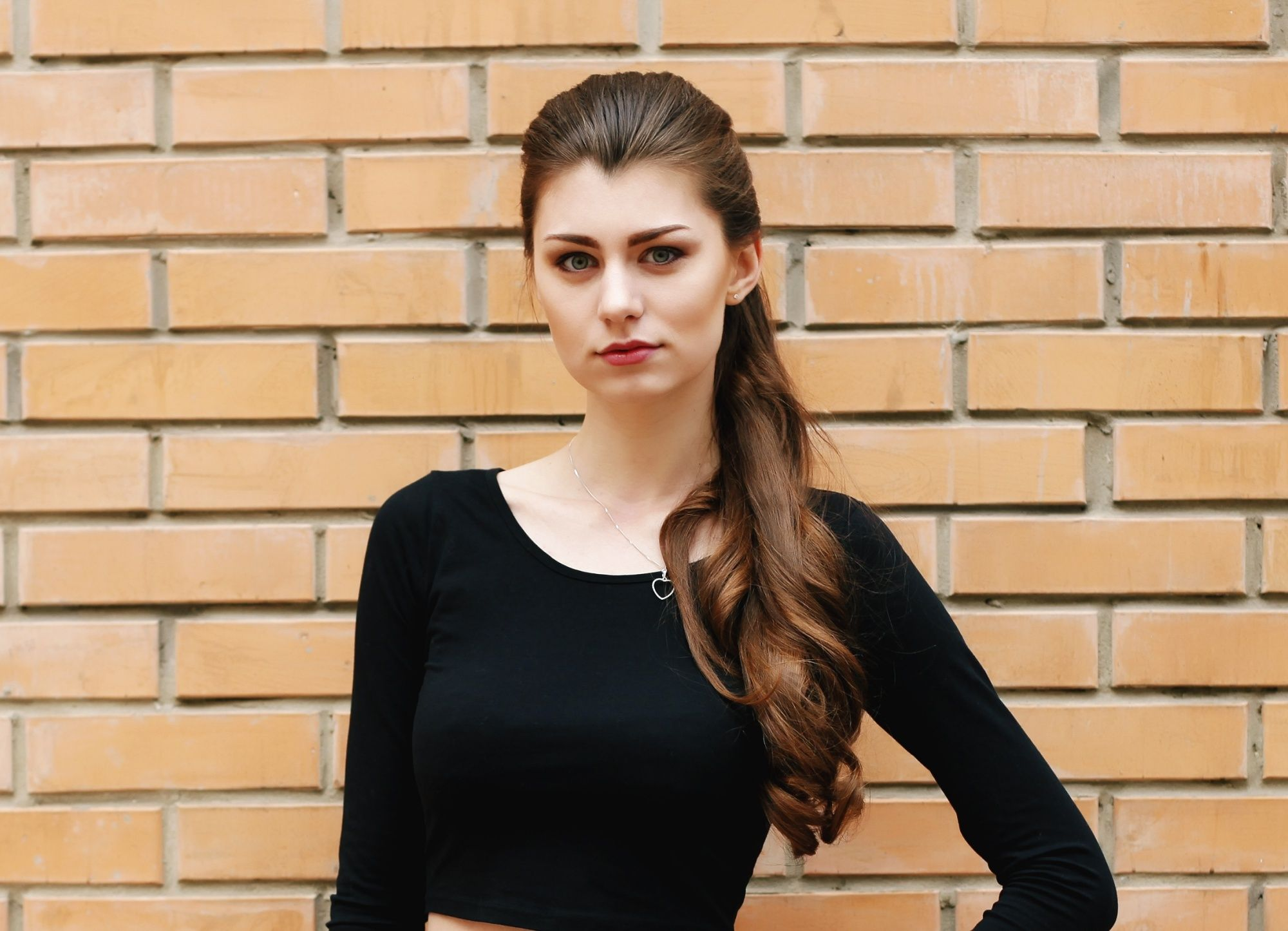 Caramel hair color: Woman with long brown hair in a ponytail against a brick wall