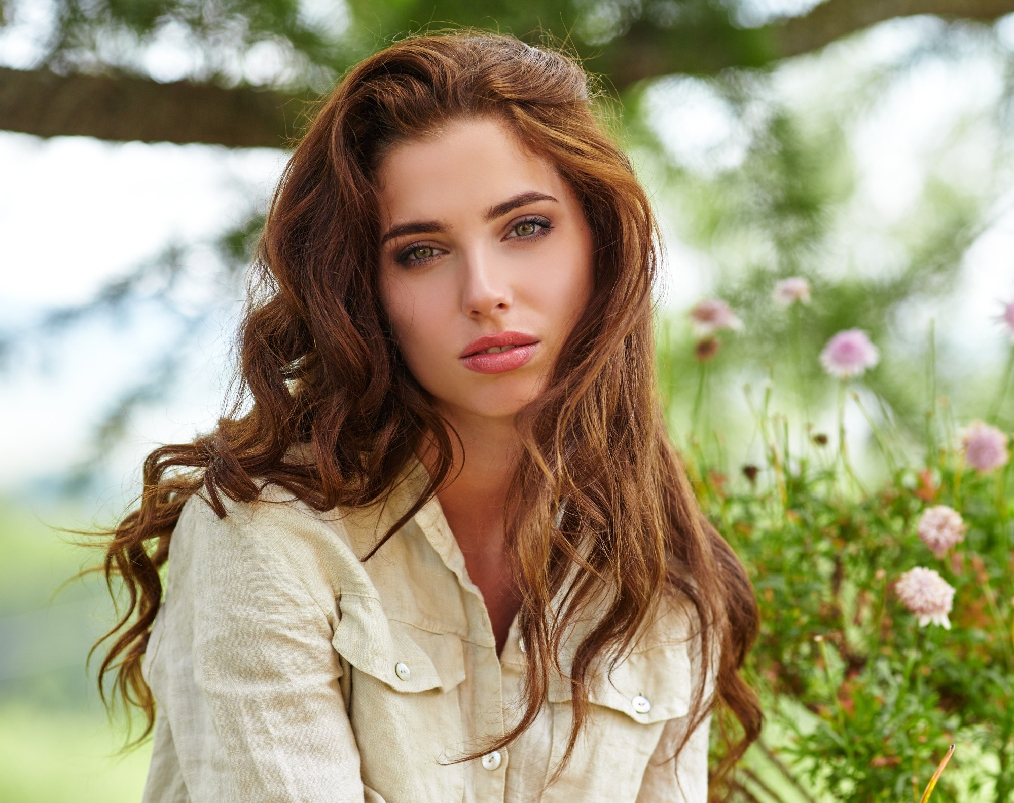 Caramel hair color: Woman with long brown hair wearing a white blouse outdoors