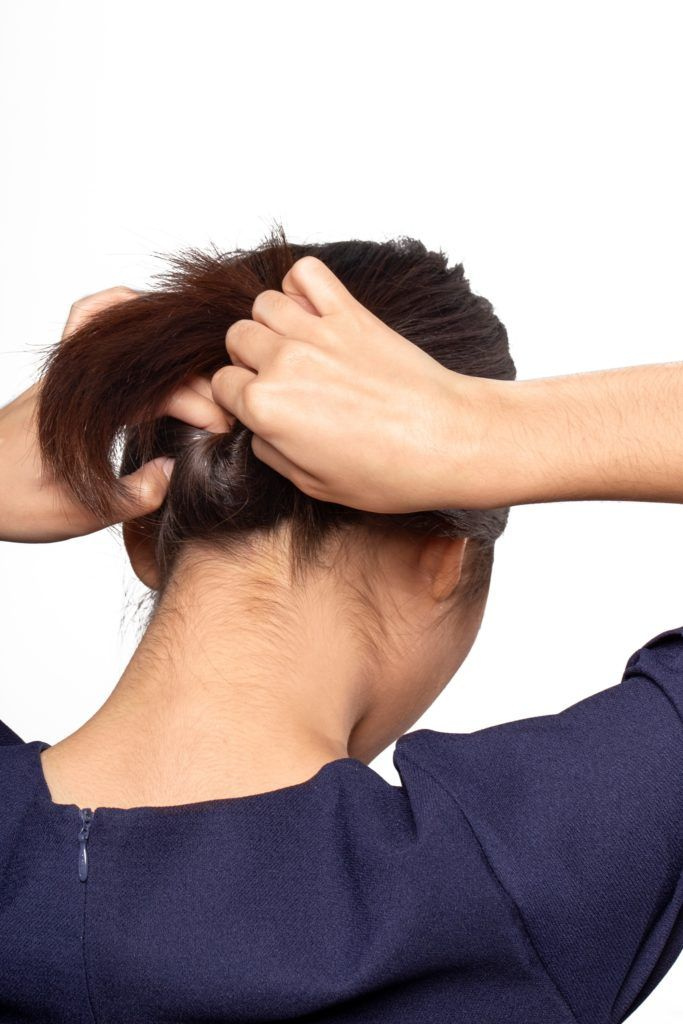Chignon for short hair: Back shot of an Asian woman with dark brown hair tucking her ponytail into a gap