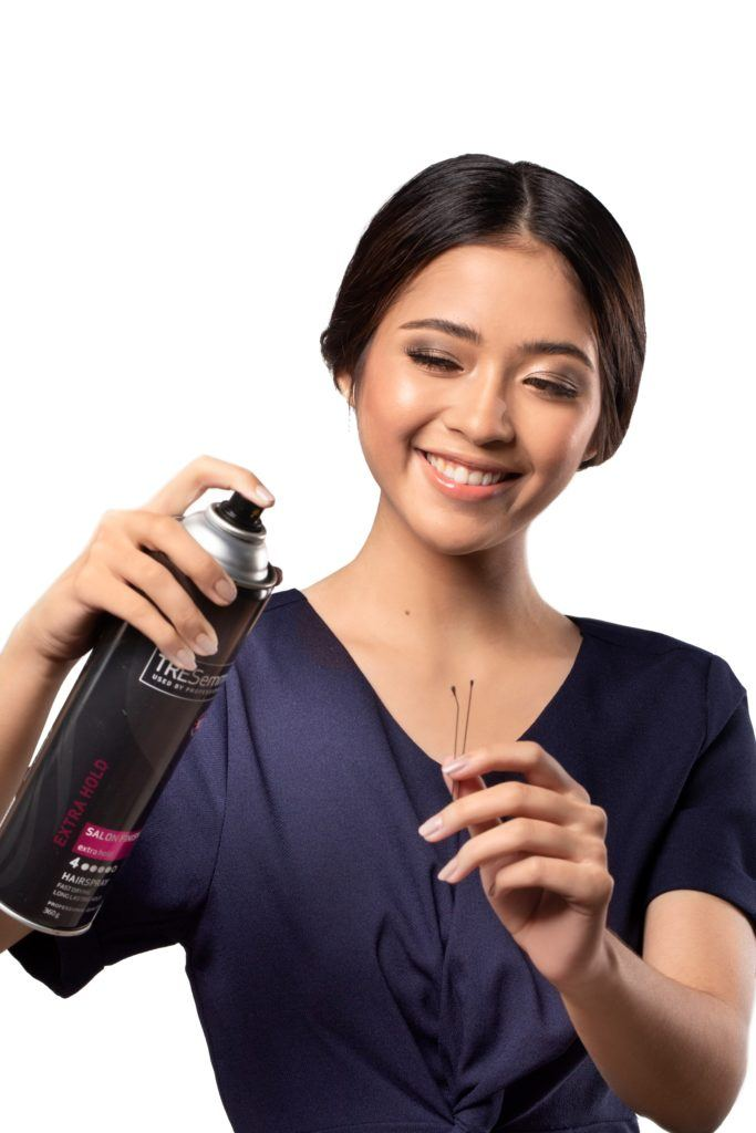 Chignon for Short Hair: Asian woman with dark hair in chignon spraying hairspray on a bobby pin